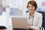 Happy young businesswoman working on laptop