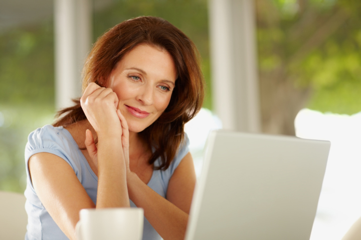 Beautiful mature female looking at laptop